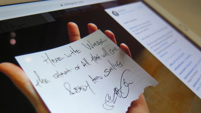 Screenshot: Auf einem iPad ist ein Foto auf Instagram zu sehen. Es zeigt eine Hand, die einen Zettel mit einem Gedicht hält.