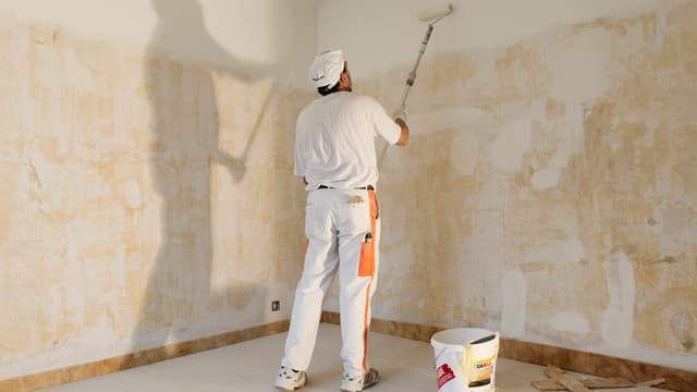 Berufsmaler streicht Wand