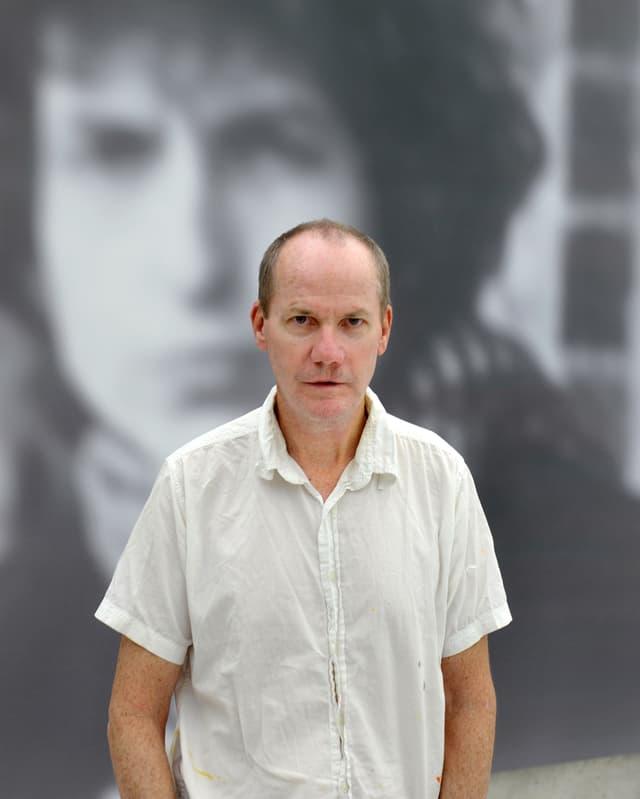 Der Künstler Richard Prince steht in einem Kurzarmhemd vor einem seiner Gemälde.