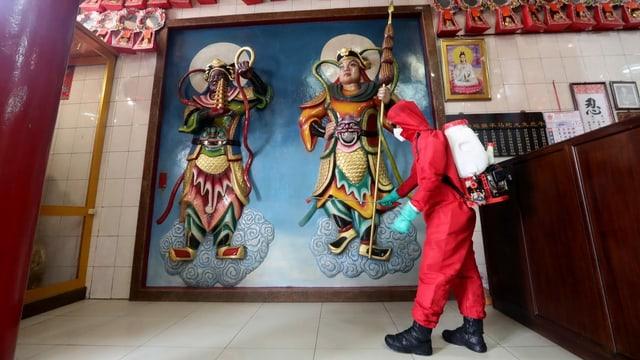 Mann desinfiziert den Nana Dasana Temple in Jakarta.