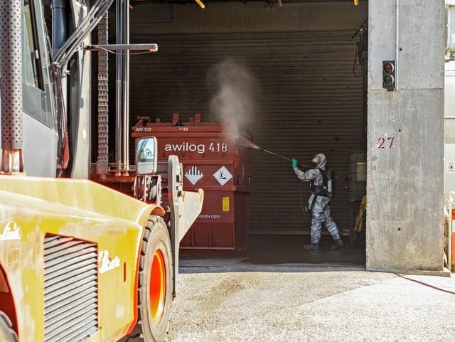 Ein Mann spritzt Wasser auf einen Container