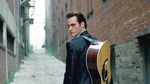 Ein Mann mit Gitarre auf dem Rücken.