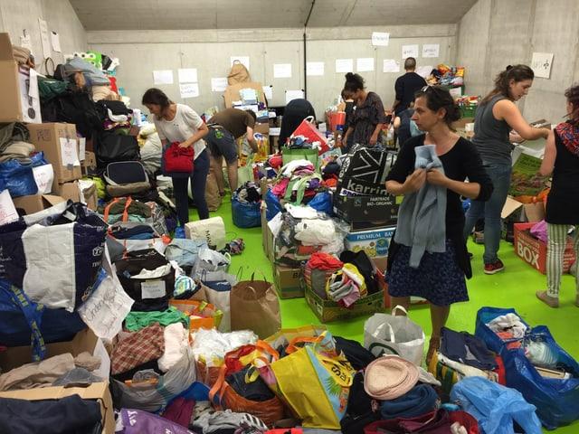 Im Lager staplen sich Sachspenden, die von Helfern sortiert werden