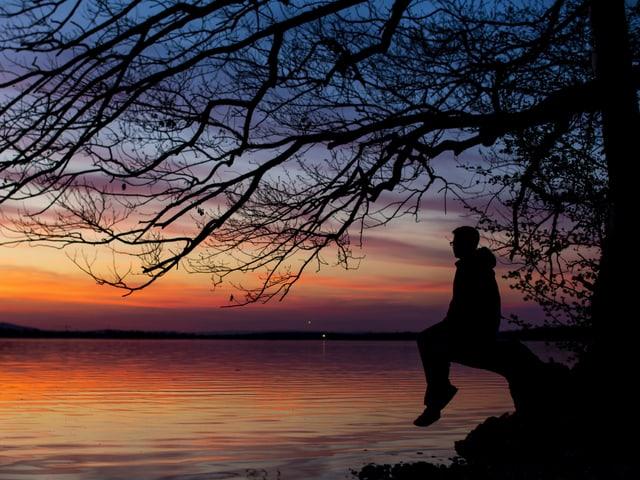 Oranger Himmel spiegelt sich in einem See. Ein Mann sitzt am Ufer unter einem Baum im Gegenlicht und geniesst die Stimmung