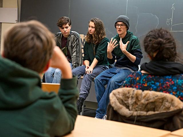 Drei Jugendliche sitzen auf dem Lehrerpult vor der Wandtafel und sprechen zu der Schulklasse.
