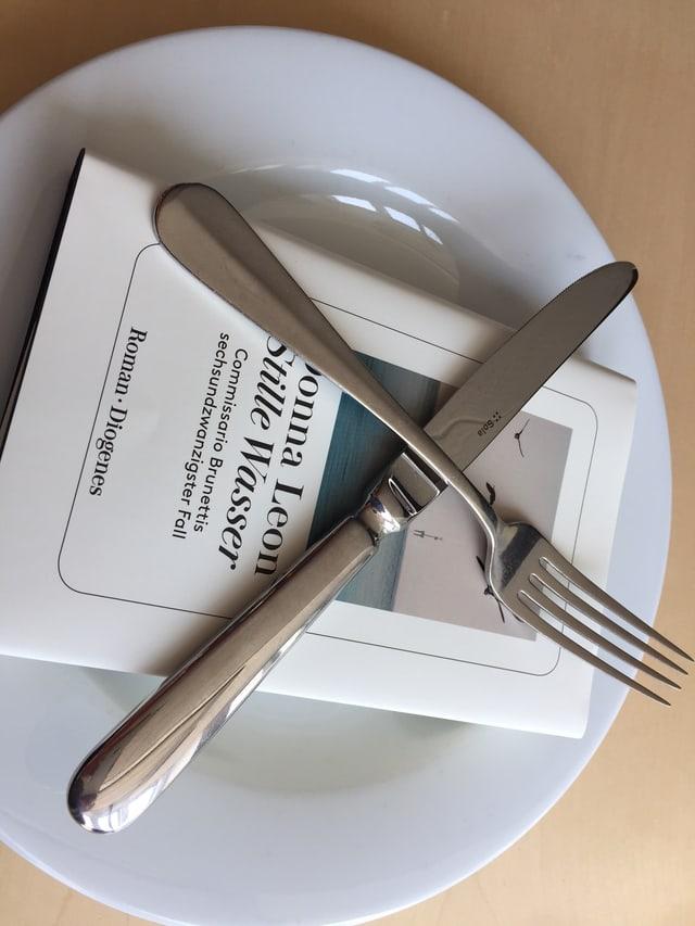 Der neue Krimi «Stille Wasser» von Donna Leon auf einem weissen Teller. Das Besteck gekreuzt darüber.