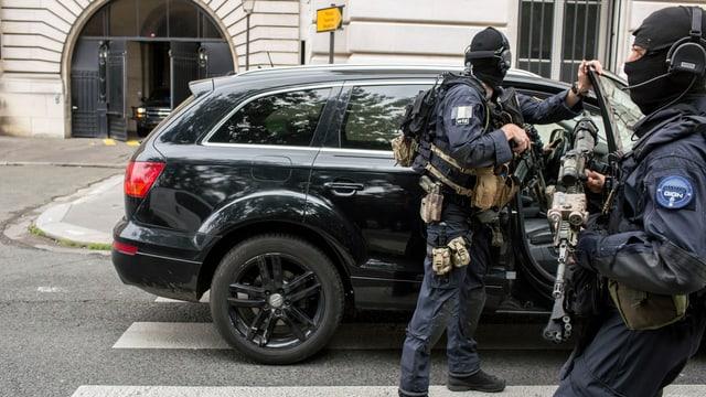 Zwei bewaffnete Männer vor einem schwarzen Auto.