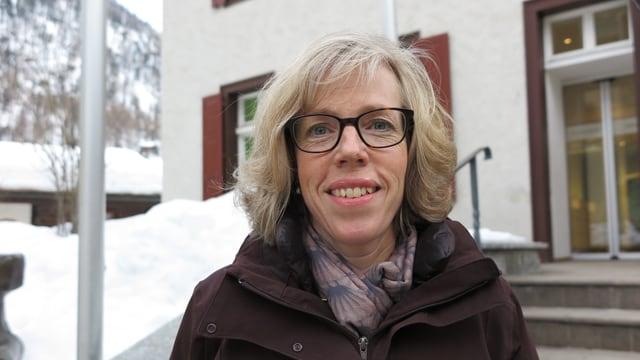 Eine Frau blickt in die Kamera. Im Hintergrund ist eine Treppe, daneben viel Schnee.