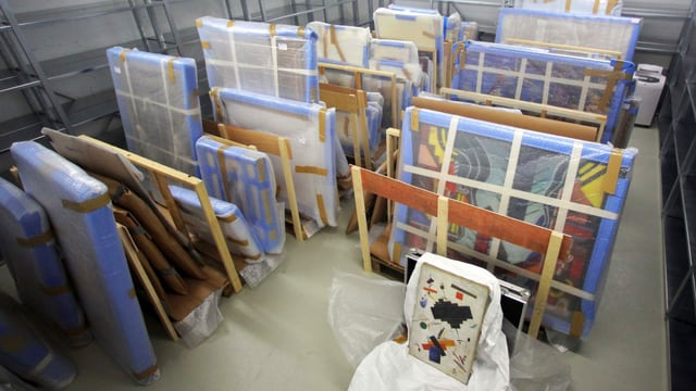 Zahlreiche verpackte Bilder stehen aufgestellt am Boden.
