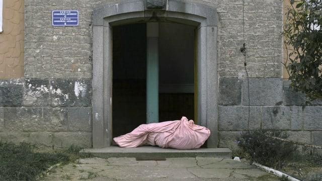 Zwei Männer deponieren einen in rosa Tuch eingewickelten Menschen vor einer Türe, klopfen an und verschwinden schnell.