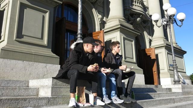 Drei Jugendliche beim Picknick auf der Eingangstreppe zum Stadttheater Bern.
