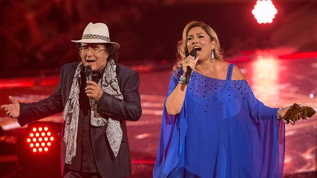 Ein singendes Paar auf einer Konzertbühne.