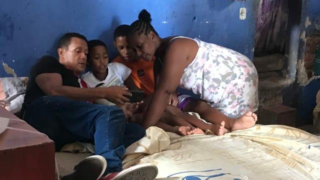 Eine Familie (Vater, Mutter und zwei Söhne) sitzen auf einem Bett und sehen sich etwas auf dem Smartphone an.