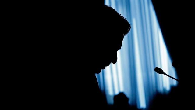 Die Silhouette eines Mannes am Mikrofon.