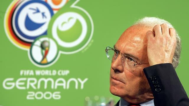 Beckenbauer kratzt sich am Kopf, hinter ihm das Logo der Fussball-WM 2006.