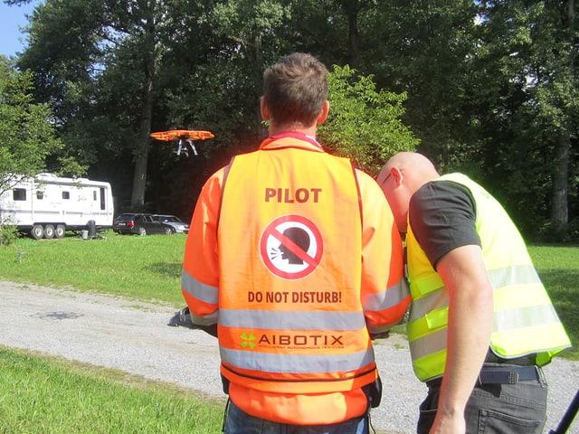 Zwei Männer von hinten, im Hintergrund der orange Multikopter.