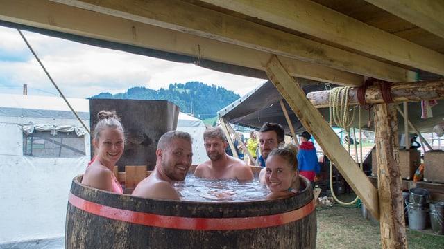 Mitglieder der Pfadi Rothenburg kühlen sich im Kantonslager «LUpiter 18» ein einem grossen Bottich voller Wasser ab.