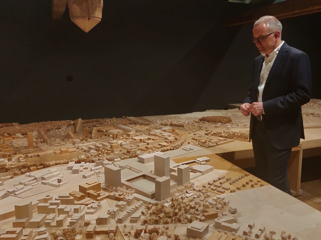 Mann mit Brille schaut auf Modell einer Stadt.