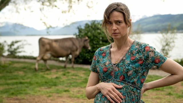 Schwangere Frau mit dickem Bauch steht am Ufer eines Sees. Hinter ihr steht eine Kuh.