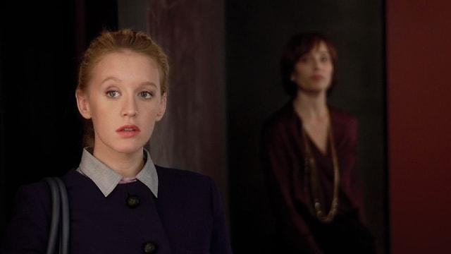 Im Vordergrund eine blonde Frau mit verdutzdem Blick dahinter eine dunkelhaarige Frau.