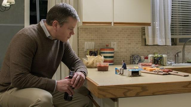 Ein Mann sitzt in einer Küche an einer Bar. Auf der Bar stehen Chips, Salsa und ein kleiner Mann, der auf einer Cracke-Schachtel sitzt. Die beiden unterhalten sich.