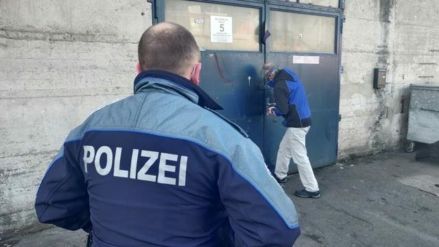 Mann öffnet Türschloss, Polizist schaut zu.