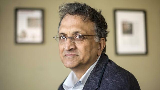 Ein indischer Mann mit Hemd, Jackett und Brille.