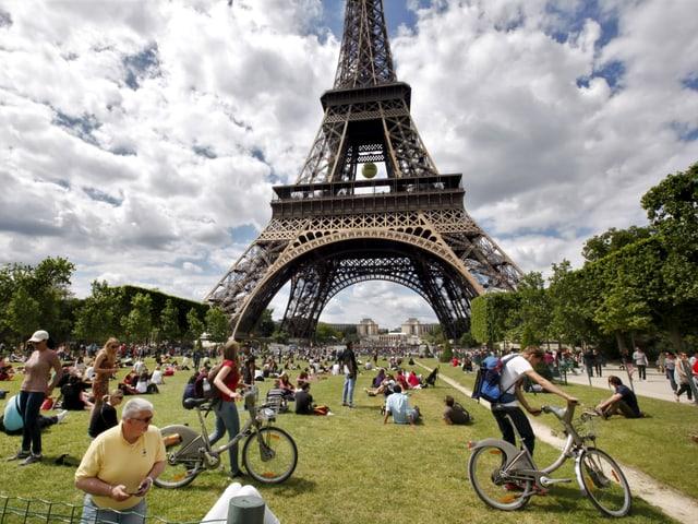 Touristen liegen auf einer Rasenfläche vor dem Eiffelturm.