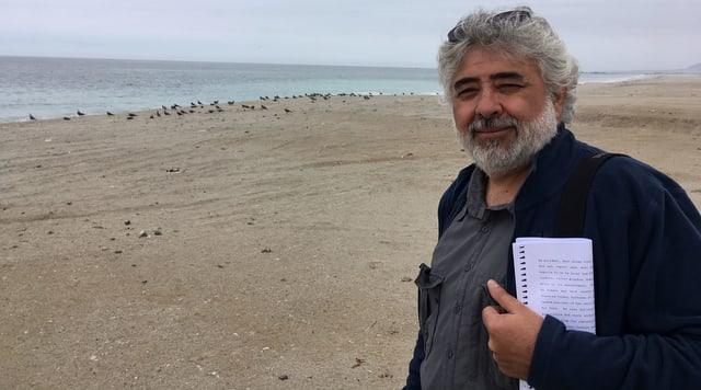 Ein Mann mit grauem Haar am Strand.