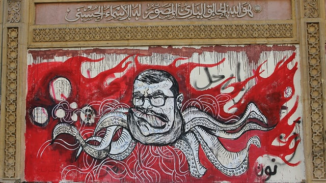 Abbildung eines Graffitos: Vor roten Flammen ist in schwarz-weiss der Kopf Mursis mit Brille abgebildet, von dem Tentakel-Arme abgehen.
