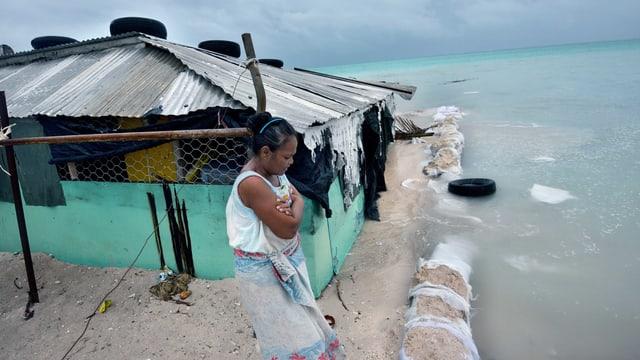 Eine Frau steht auf dem Festland und schaut mit verschränkten Armen auf die Wassermassen des Meeres, die bereits ihr Haus erfasst haben.