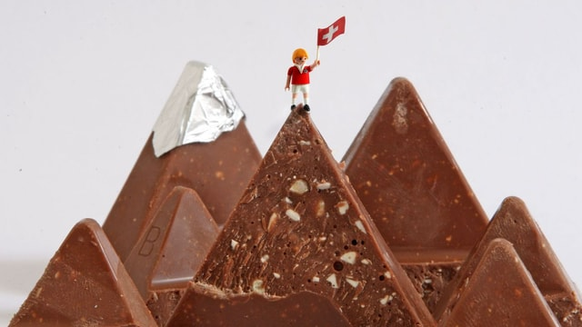 Ein Playmobil-Männchen steht auf Berggipfeln aus Schokolade