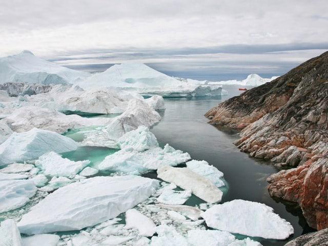 Ein winziges rotes Boot schwimmt im Meer, in dem sich riesige Eisschollen befinden.