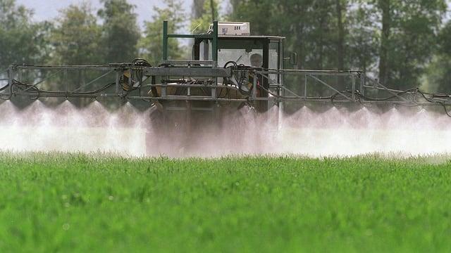 Ein Bauer bringt auf dem Feld Pflanzenschutzmittel aus.