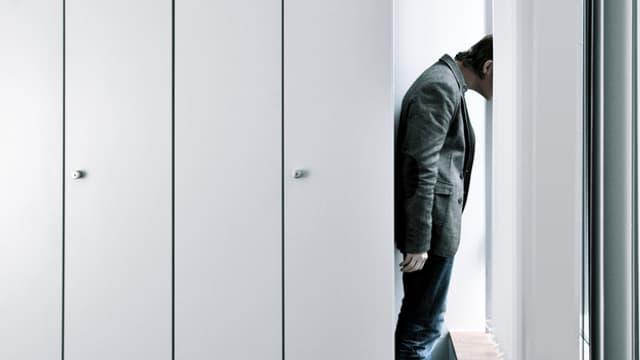 Mann steckt seinen Kopf zwischen die Lamellen einer Bürojalousie.