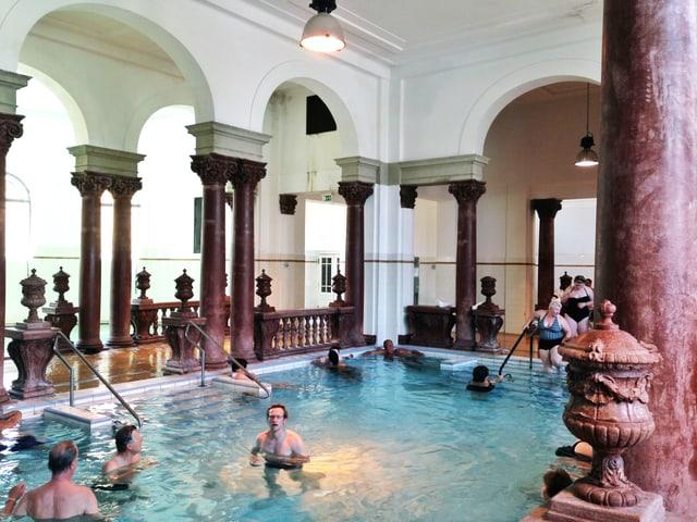 In einem hohen Innenbad sind einige Menschen in hellblauem Wasser.