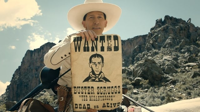 Ein Cowboy hält ein Plakat hin. Darauf steht: Wanted.