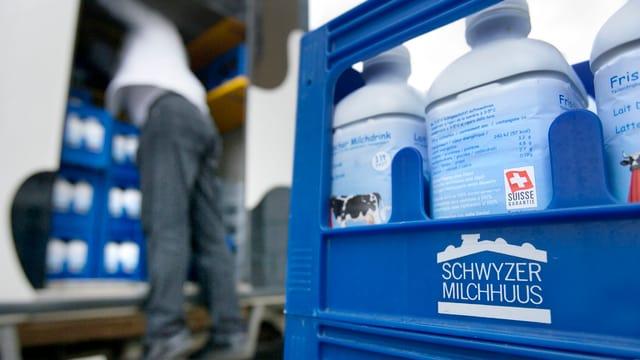 Milch in Harassen, im Hintergrund ein Mann der sie aus einem Lastwagen auslädt.