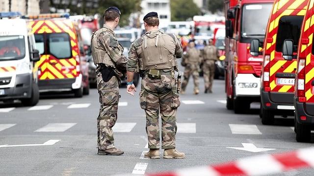 Polizisten und Rettungswagen auf einer Strasse. Davor Absperrungsband.