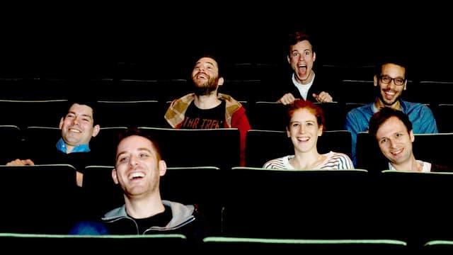 7 Personen sitzen lachend in Kino-Sitzreihen.