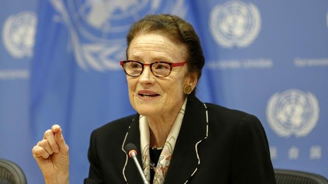 Eine ältere Frau vor einem blauen Hintergrund am Mikrofon.