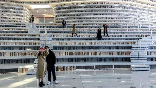 Grosser Raum mit riesigen, mehrstöckigen weissen Bücherregalen. Mehrere PErsonen sind zu sehen, die mit Handys Fotos machen.
