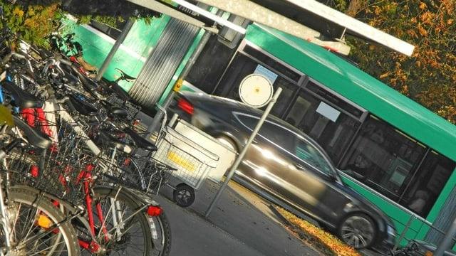 Verkantete Aufnahme mit 6er-Tram, Auto und Veloständern an Tramstation in Riehen.
