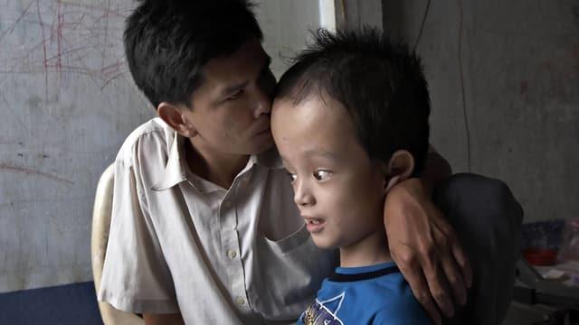 Ein Mann hält seinen behinderten Sohn im Arm.