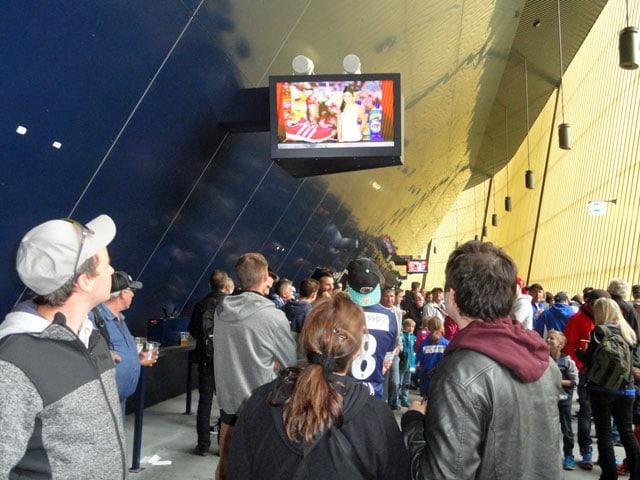 Personen stehen betrachten das Geschehen auf einem aufgehängten Bildschirm.