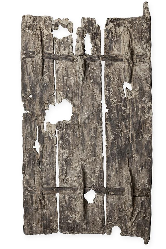 Eine Tür aus drei Brettern mit Löchern.