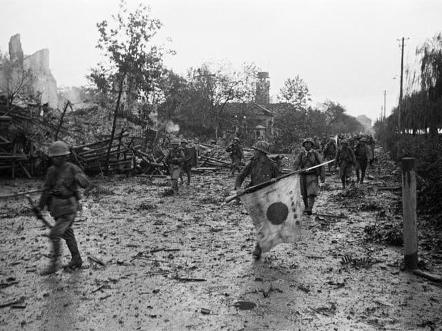 Japanische Soldaten gehen durch eine zerbombte Stadt.
