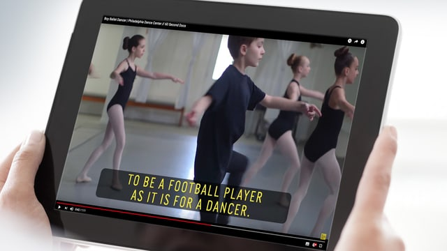 Ein Junge, der tanzt. Man sieht ihn auf einem Bildschirm.