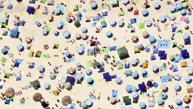 Flugaufnahme eines Sandstrands mit zahlreichen Sonnenschirmen, Zelten und Menschen auf Badetüchern.