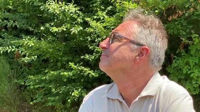 Ein Mann mit Brille in der Natur.